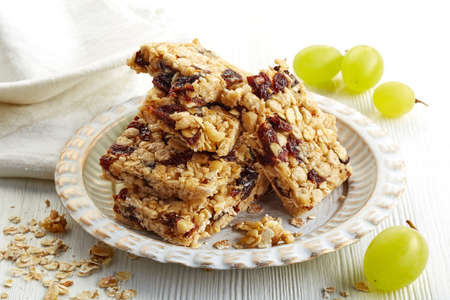 granola bar: Granola bars with raisins and grapes on white wooden background