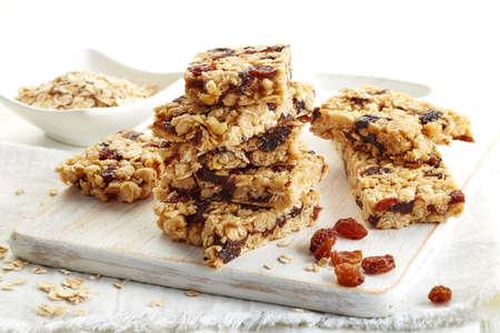barra de cereal: Barra de granola con pasas en el fondo de madera blanca Foto de archivo