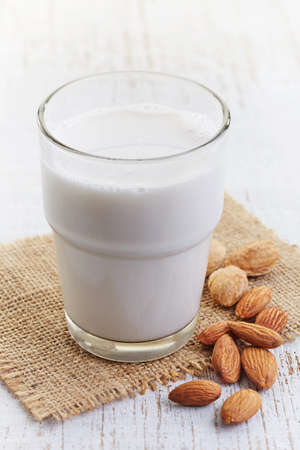almond: Glass of almond milk  on white wooden background Stock Photo