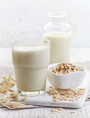 Glass of oat milk on white wooden background Stockfoto