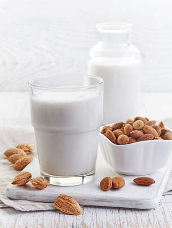 Glass of almond milk  on white wooden background Stockfoto