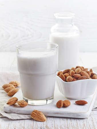 Verre de lait d'amande sur fond blanc bois Banque d'images