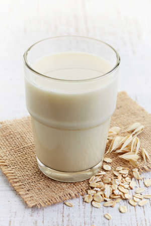 Glass of oat milk on white wooden background Banque d'images