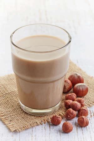 avellanas: Vaso de leche de avellana en el fondo de madera blanca