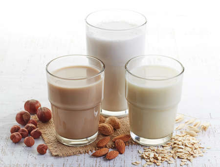 glass of milk: Different vegan milk: almond milk, hazelnut milk and oat milk