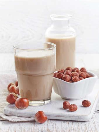 alimentos y bebidas: Vaso de leche de avellana en el fondo de madera blanca
