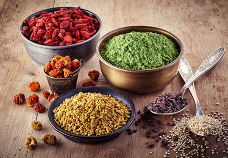 vegan: Bowls and spoons of various superfood on wooden background