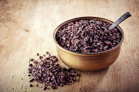crushed: Bowl of cacao nibs on wooden background Stock Photo
