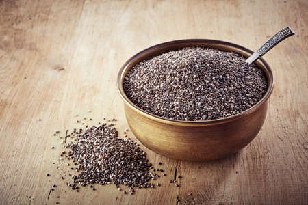 a seed: Bowl of chia seeds on wooden background Stock Photo