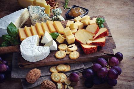 チーズ プレートは、ブドウ、ジャム、クラッカー、木製の背景上のナッツを添えてください。クローズ アップ。