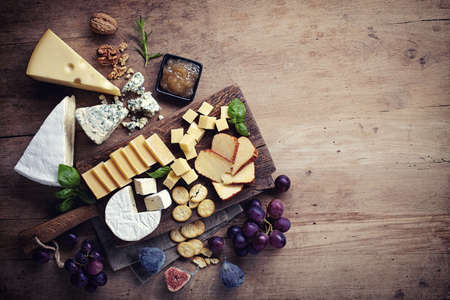 cutting boards: Cheese plate served with grapes, jam, figs, crackers and nuts on a wooden background Stock Photo