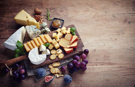 Cheese plate served with grapes, jam, figs, crackers and nuts on a wooden background Stock Photo