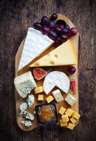 Assiette de fromages servi avec des raisins, des confitures et des figues sur un fond en bois