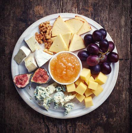 Assiette de fromages servi avec des raisins, de la confiture, des figues et des noix sur un fond en bois