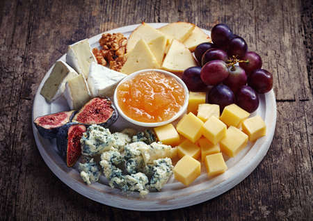 white board: Cheese plate served with grapes, jam, figs and nuts on a wooden background Stock Photo