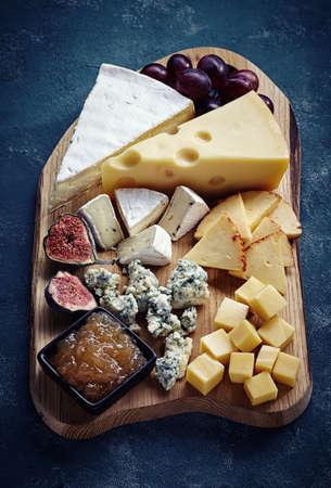 tabla de quesos: Placa de queso servido con uvas, mermelada y los higos en un fondo azul