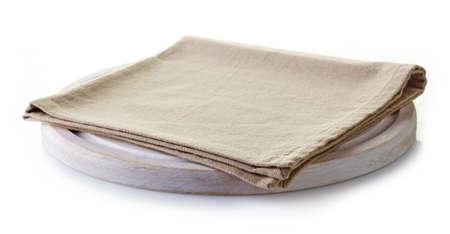 servilleta: Servilleta de algod�n beige sobre una tabla de cortar blanco aislado en fondo blanco