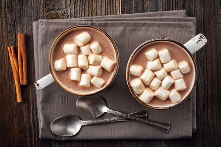 Two cups of hot cocoa with marshmallows and cinnamon sticks on wooden background