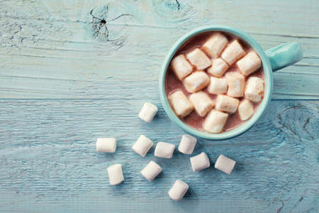coffee table: Blue cup of hot cocoa with marshmallows on blue wooden background
