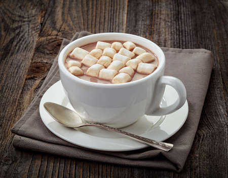 wooden table: White cup of hot cocoa with marshmallows on wooden background Stock Photo