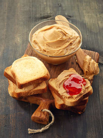 peanut butter and jelly sandwich: Bowl of peanut butter, peanut butter strawberry jelly sandwich and peanuts on wooden cutting board and wooden background Stock Photo