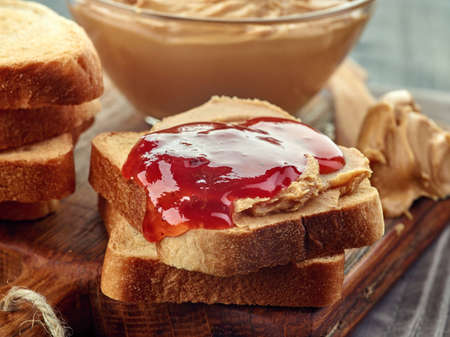 strawberry jelly: Bowl of peanut butter and peanut butter strawberry jelly sandwich on wooden cutting board. Close-up.