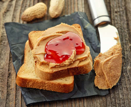 peanut butter and jelly sandwich: Peanut butter and strawberry jelly sandwich on wooden background