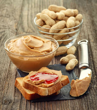strawberry jelly: Peanut butter and strawberry jelly sandwich with bowl of peanuts and peanut butter on wooden background