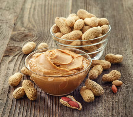Bowl of peanut butter and peanuts on wooden background