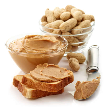 Peanut butter sandwich, bowl of peanut butter, peanuts and a knife isolated on white background