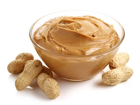 Glass bowl of peanut butter with peanuts isolated on white background Standard-Bild