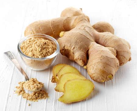 Riz au gingembre fraîchement cueilli et gingembre moulu sur fond blanc en bois
