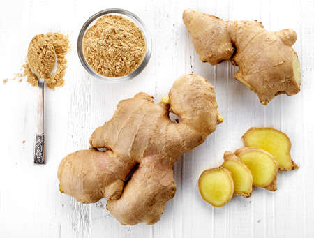 Fresh sliced ginger root and ground ginger on white wooden background; top view