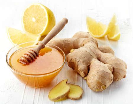 ginger health: Fresh ginger root, honey and lemon on white wooden background Stock Photo