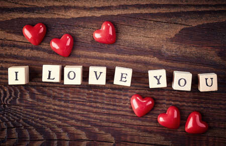 love shape: Wooden cubes with text I love you on wooden background from top view Stock Photo