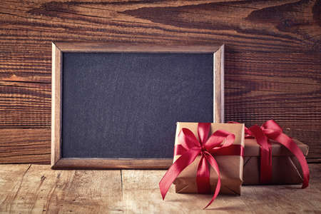 text box design: Blackboard and gift boxes on wooden background Stock Photo