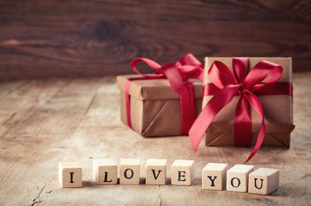 felicitaciones cumplea�os: Brown gift boxes and wooden cubes with text I love you on wooden background