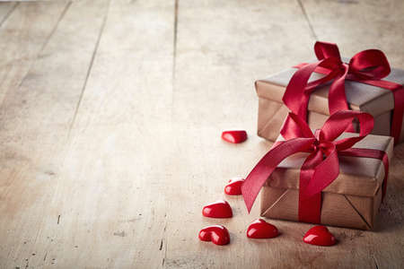 text box design: Two brown gift boxes with red ribbons on wooden background