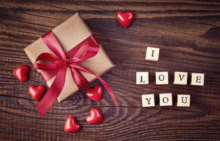 felicitaciones cumplea�os: Caja de regalo y los cubos de madera con el texto Te amo en el fondo de madera de la vista