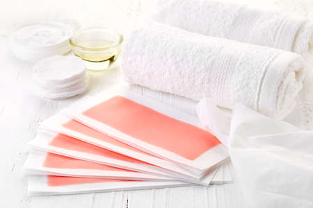 cotton pad: Pink waxing strips, cream and body oil on white wooden background