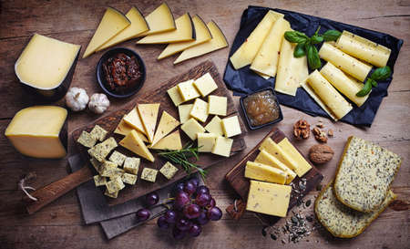 Cheese plates served with grapes, jam, figs, crackers and nuts on a wooden background, Top view
