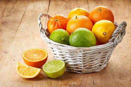 Basket of citrus fruits on wooden background