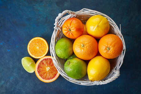 fruits in a basket: Basket of citrus fruits on dark blue background from top view