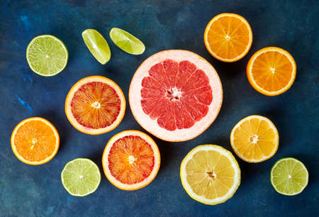 lemon slice: Various colorful citrus fruits on blue background, Top view Stock Photo