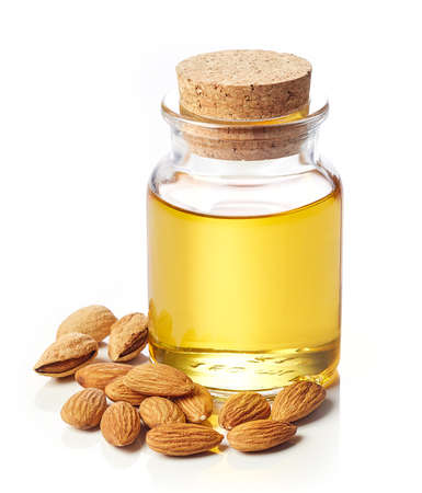 Bottle of almond oil and almonds isolated on white background
