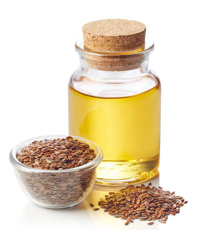 Bottle of linseed oil and bowl of linseeds isolated on white background