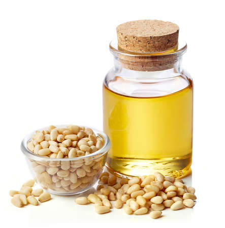 pinoli: Bottiglia di olio di pinoli e ciotola di pinoli isolato su sfondo bianco