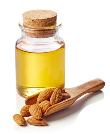 Bottle of almond oil and wooden scoop of almonds isolated on white background