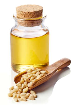 pinoli: Bottiglia di olio di noce di pino e legno scoop di pinoli isolato su sfondo bianco