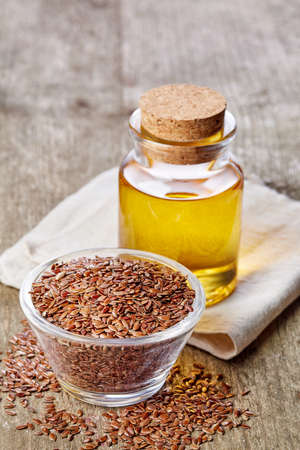 linseed oil: Bottle of linseed oil and bowl of linseeds on wooden background Stock Photo
